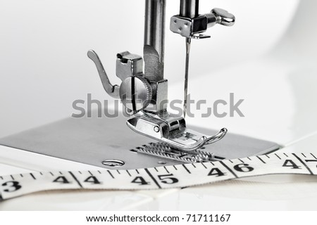 Macro view of a sewing machine mechanism and a measuring tape