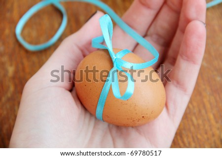Macro view of egg with a blue bow on a female hand