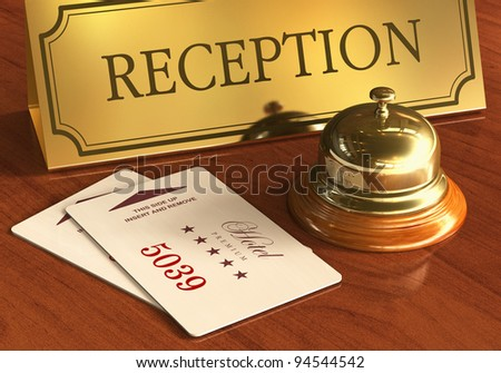 Macro view of golden service bell and room access cardkeys on wooden reception desk in hotel