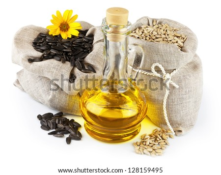 Macro view of purified and raw sunflower seeds in flax sacks and glass bottle of sunflower oil isolated on white background