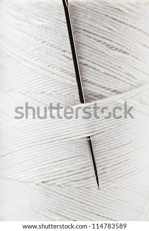 Macro view of reel of white thread with needle