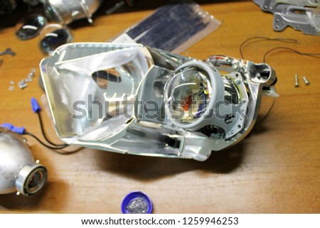 Macro view of repairing, installation and turning headlight of modern automobile and car projector lens. Vehicle head xenon lamp in details. Concept of auto detailing, light and LED technology