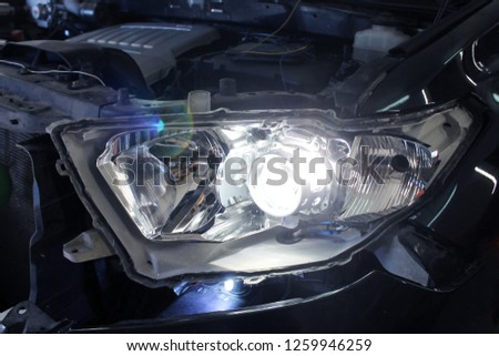 Macro view of repairing, installation and turning headlight of modern automobile and car projector lens. Vehicle head xenon lamp in details. Concept of auto detailing, light and LED technology #1259946259