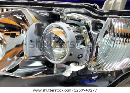 Macro view of repairing, installation and turning headlight of modern automobile and car projector lens. Vehicle head xenon lamp in details. Concept of auto detailing, light and LED technology #1259949277