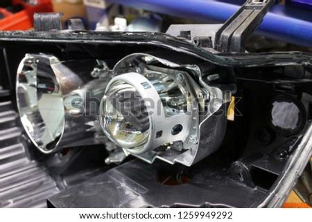 Macro view of repairing, installation and turning headlight of modern automobile and car projector lens. Vehicle head xenon lamp in details. Concept of auto detailing, light and LED technology #1259949292