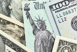 Macro view of the Statue of Liberty on a United States Treasury Check surrounded by currency.