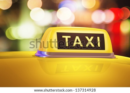 Macro view of yellow taxi sign on car in evening or night city street outdoors