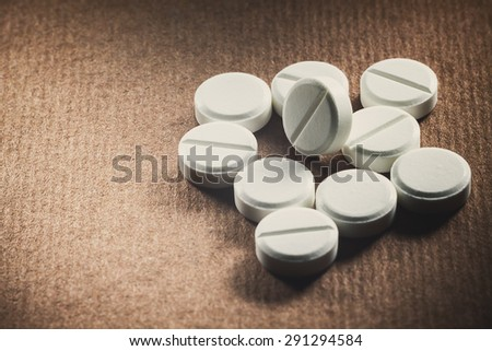 Macro view on white tablets, unpacked on blurry brown background with empty space on left side.