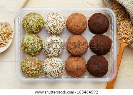 macrobiotic healthy food: balls from ground wheat sprouts with sesame, pumpkin seeds and chocolate sprinkles in plastic box; sprouted grains in wooden spoon on table, top view