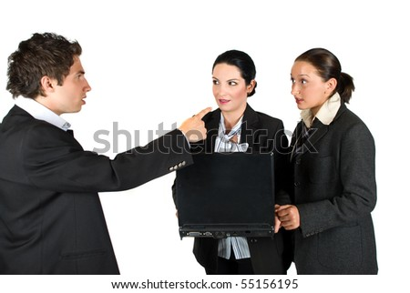 Mad boss screaming at his employers while the two  woman holding and using a laptop and looking very surprised and shocked at him - stock photo