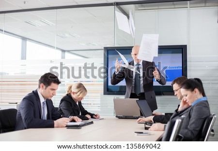 Mad CEO throwing documents at a meeting. Subordinates looking down, afraid to make eye contact.