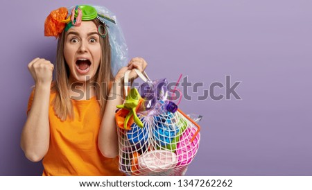 Mad emotive young woman of European appearance reacts emotionally on having duties, works in protective environmental organization, carries bag of trash, isolated over lilac wall with free space #1347262262