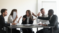 Mad frustrated multiethnic employees sit at office meeting dispute quarrel have stressful job situation, angry diverse colleagues debate fight over paperwork financial statistics, work stress concept
