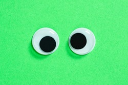 Mad googly eyes on neon green background, cross-eyed funny toys eyes close-up.