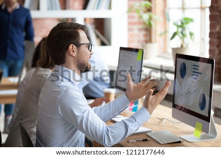 Mad male employee look at screen nervous about computer operation problem, angry man sit in shared office gesturing unhappy about pc malfunction, having slow internet connection or data loss