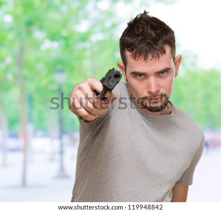 mad man pointing with gun, outdoor