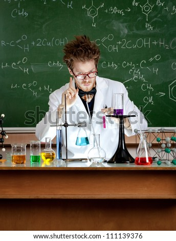 Mad professor shows attention gesture in his laboratory