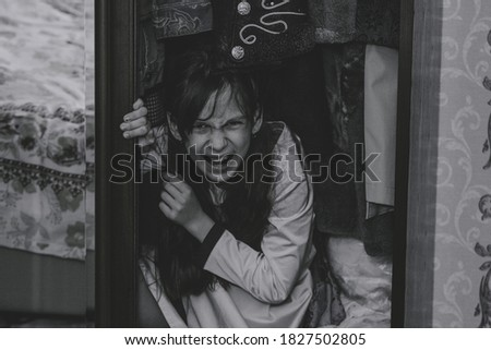 Mad scary girl in cupboard at dark night. Horror background with child possessed by devil. Demon possessed little girl in closet at night. Ghost of little girl at dark night. Child ghost in cupboard. Stock photo ©
