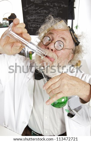 Mad senior scientist in lab concentrates on pouring green liquid into beaker. Frizzy grey hair, round glasses, lab coat, blackboard, vertical, high key, copy space. - stock photo