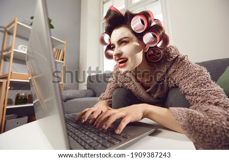 Mad woman in face mask and hair rollers sitting looking at laptop computer screen, writing insulting hater comment, spreading fake rumour. Jealous wife reading husband's direct message on social media Stock photo ©