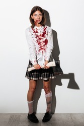 Mad woman in zombie make up covered with blood stains standing and holding an axe isolated over white background