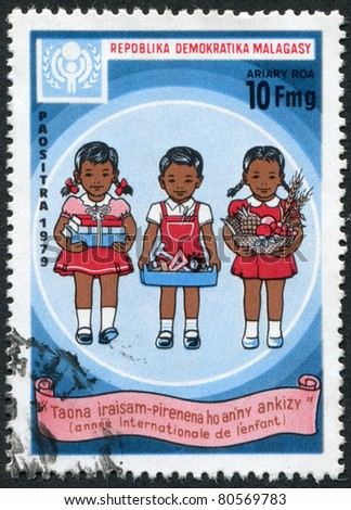 MADAGASCAR - CIRCA 1979: Postage stamps printed in Madagascar, is dedicated to International Children\'s Day, shows the children with books, toys, fruits, circa 1979