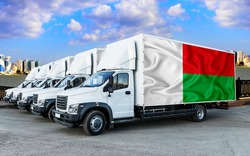 Madagascar flag on the back of Five new white trucks against the backdrop of the river and the city. Truck, transport, freight transport. Freight and Logistics Concept