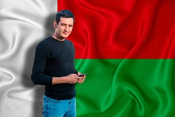 Madagascar flag on the background of the texture. The young man smiles and holds a smartphone in his hand. The concept of design solutions.
