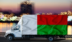 Madagascar flag on the side of a white van against the backdrop of a blurred city and river. Logistics concept