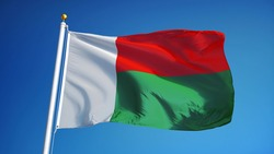 Madagascar flag waving against clean blue sky, close up, isolated with clipping path mask alpha channel transparency