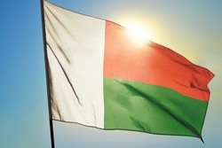 Madagascar flag waving on the wind in front of sun