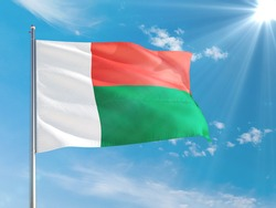 Madagascar national flag waving in the wind against deep blue sky. High quality fabric. International relations concept.