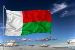 Madagascar national flag waving in the wind against deep blue sky.  International relations concept.