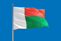 Madagascar national flag waving in the wind on a deep blue sky. High quality fabric. International relations concept.