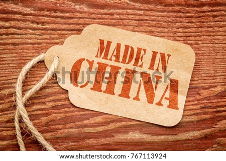 made in China  sign - red stencil text on a paper price tag against grunge wood #767113924