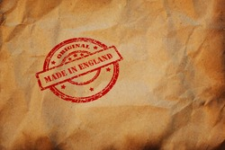 Made in England stamp printed on crumpled sheet of burnt paper. English product, parcel, package, seervice, production logistics concept. Background with copyspace for design.