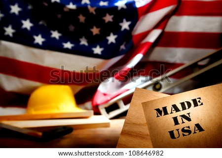 Made in USA stencil stamp logo on brown recycled paper over a carpentry wood board at an American construction work site in the United States with patriotic US flag and trade working tools background