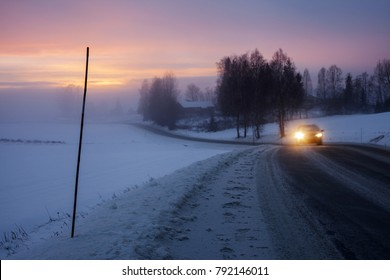 Stock photo made at roadside at winter evening in Scandinavia. Dusk, fog and misty sunset at background. Car approaching with headlights on. Focus on temporary pole for winter marking at left.