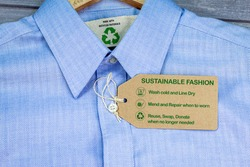 Made with recycled materials shirt with sustainable fashion care label, fashion wash cold, line dry, mend and repair, reuse, swap or donate with icons.
