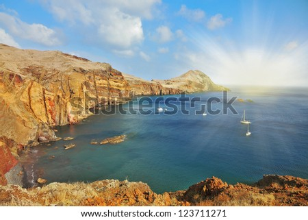 Madeira. Picturesque white yachts in the rocky gulf in the east of the island. Shining rays of the sun reflected in the water - stock photo