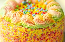 Madeira sponge coated with yellow colour frosting, layered with plum and raspberry jam, filled and topped with multicolour chocolate nibs and decorated with  frostings and sugar decorations, pinata ca