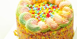 Madeira sponge coated with yellow colour frosting, layered with plum and raspberry jam, filled and topped with multicolour chocolate nibs and decorated with frostings and sugar decorations, pinata cak