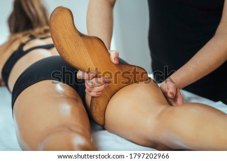 Madero therapy anti cellulite massage, masseuse massaging female back thigh muscle