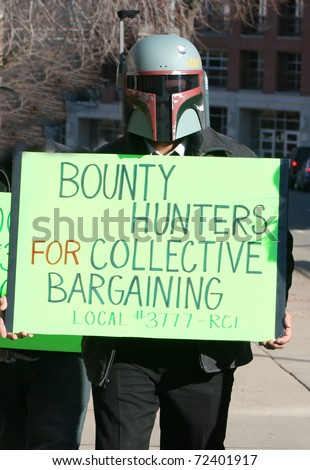MADISON, WI - FEB 19: Unidentified man protests WI Budget Repair Bill on February 19, 2011 in Madison, WI.  The man wears a Boba Fett helmet costume and holds a sign in support of union workers.