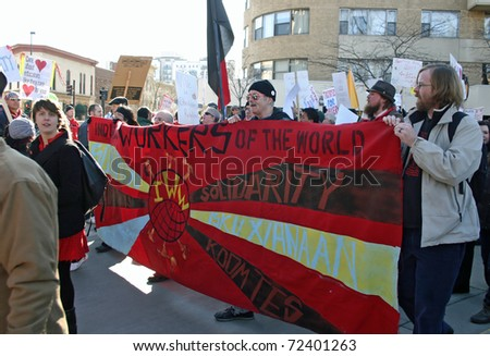 MADISON, WI - FEB 19: Unidentified people protest WI Budget Repair Bill on February 19, 2011 on the capitol square in Madison, Wisconsin.  The protesters hold a banner demonstrating solidarity.