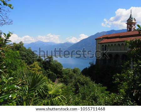 Madonna del Sasso Church above Locarno swiss city and alpine Maggiore lake at canton Ticino in Switzerland with mountainside landscapes, cloudy blue sky in 2017 warm sunny summer day, Europe on July. #1055711468