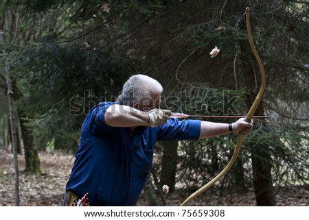 MADONNA DEL SASSO,ITALY - APRIL 17: Luigino Gattoni takes aim with a historical bow during the field archery selection for the Italian Championship Competition on April 17, 2011 in Madonna del Sasso, Novara, Italy.