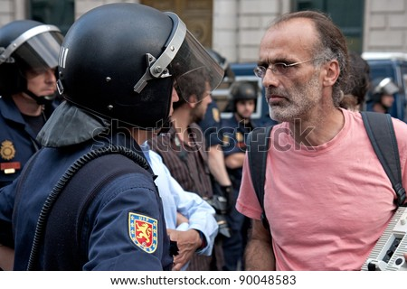 MADRID - MAY 26: Spanish Protester walking to the congress building against the spanish economic crisis and pensions for the politicians and stopped by the police on May 26, 2011.