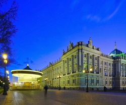 Madrid, Royal Palace - official residence seat of the Royal Family of Spain w a turning carousel beneath at blue hour