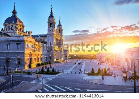 Madrid, Spain. Cathedral Santa Maria la Real de la Almudena at Plaza de la Armeria. Famous landmark with sunset sunand. Street lamps and picturesque sky with clouds.